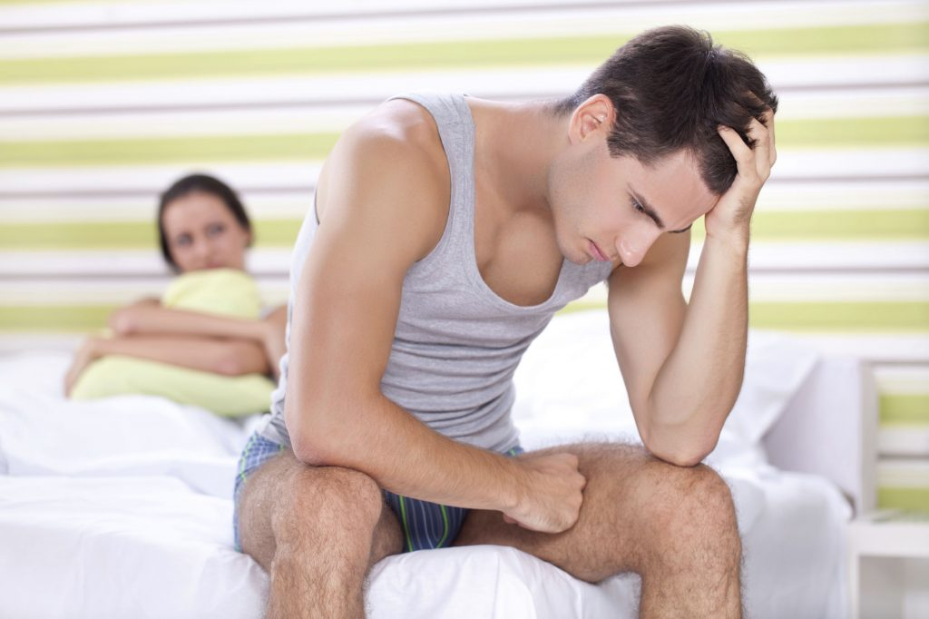 Unhappy young couple with problem in bedroom